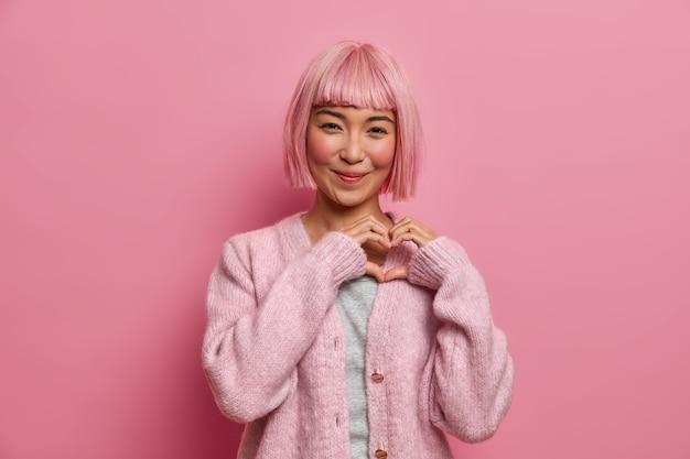 Gentille femme asiatique aimable positive avec une coiffure bob, fait un geste en forme de coeur