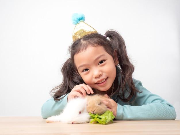 Gentille petite fille mignonne et bébés lapins blancs et bruns sur une table en bois.