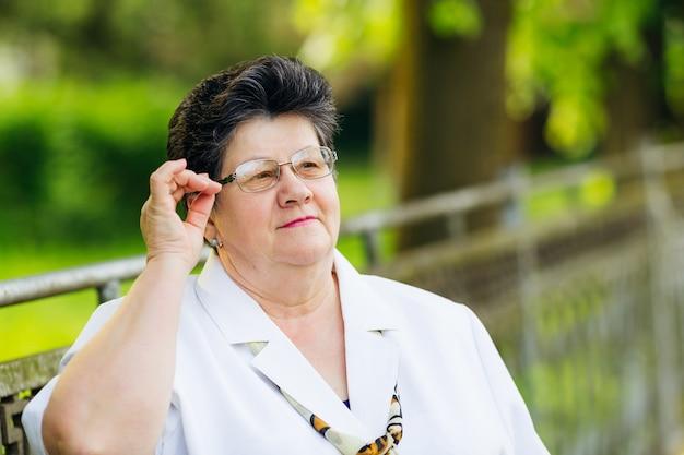 Gentille vieille femme en chemisier blanc tenant ses lunettes