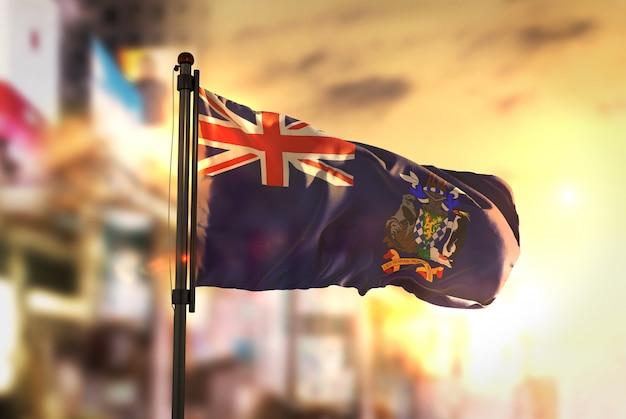 La géorgie du sud et le drapeau des îles sandwich du sud contre la ville fond floue au rétro-éclairage du réveil