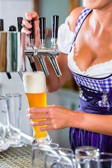 Gérant dans un pub bavarois tirant une bière