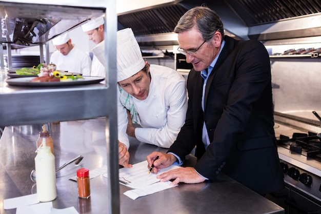 Un gérant de restaurant écrit sur le presse-papiers en interagissant avec le chef