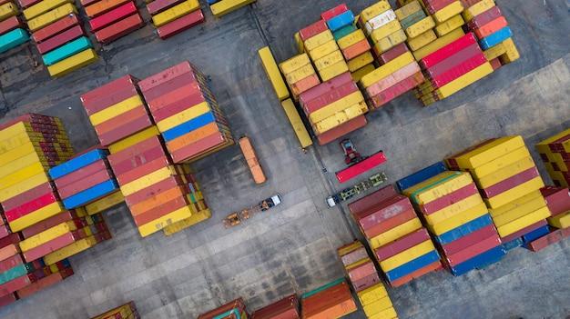 Des gerbeurs à vue aérienne déplacent des conteneurs dans un terminal de fret, un terminal à conteneurs industriel et une zone de conteneurs de stockage.
