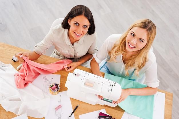 Gérer leur entreprise ensemble. vue de dessus de deux jeunes femmes travaillant ensemble alors qu'elles étaient assises sur leur lieu de travail dans un atelier de mode