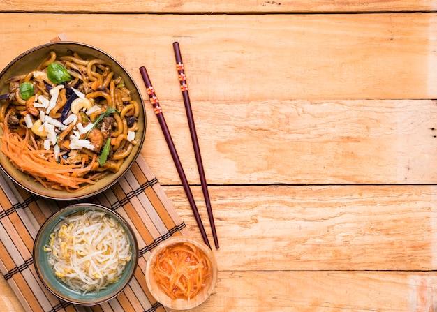 Germes de haricots; carotte râpée et nouilles avec des baguettes sur la table en bois
