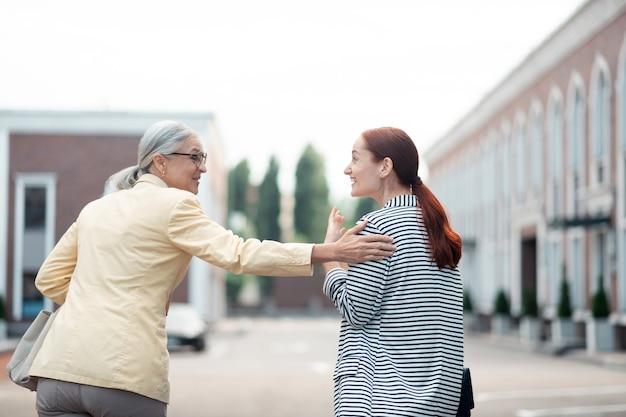 Geste amical. femme d'affaires caucasienne senior debout à l'extérieur en riant et en tapotant sa jeune collègue sur l'épaule