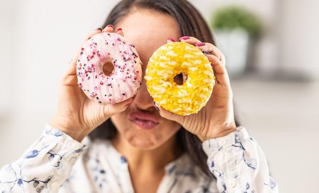 Geste amusant d'une femme regardant à travers les trous de deux types différents de beignets.