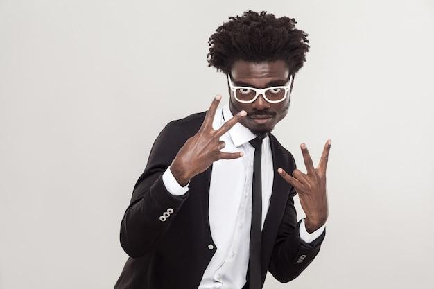 Geste de choc, cool chanter les doigts. homme africain montrant les doigts à la caméra et a un look cool. prise de vue en studio, mur gris