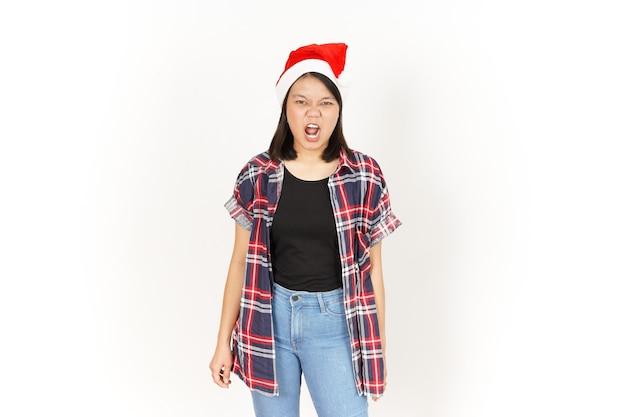 Geste en colère de la belle femme asiatique portant une chemise à carreaux rouge et un bonnet de noel isolé sur blanc
