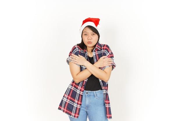 Geste de congélation de la belle femme asiatique portant une chemise à carreaux rouge et un bonnet de noel isolé sur blanc