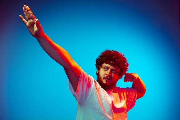Geste gagnant, succès. portrait de l'homme isolé sur le mur bleu du studio en néon. beau modèle masculin, cheveux bouclés rouges. concept d'émotions humaines, expression faciale, ventes, publicité.