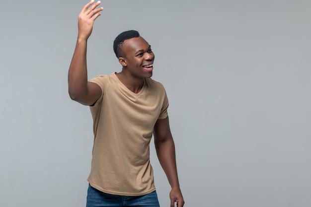 Geste joyeux. sourire joyeux homme à la peau sombre levant la main à la recherche de côté sur fond clair