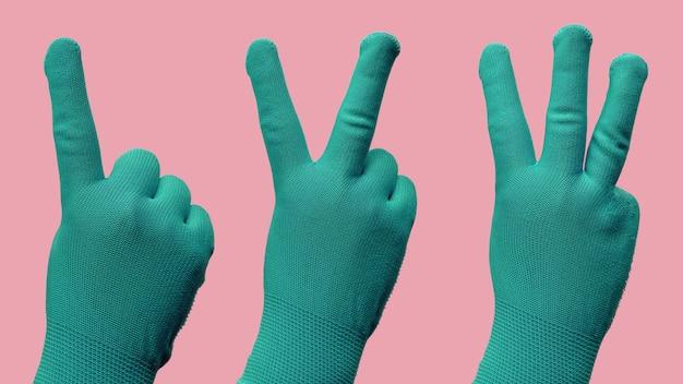 Geste de la main comme un deux trois dans les gants verts