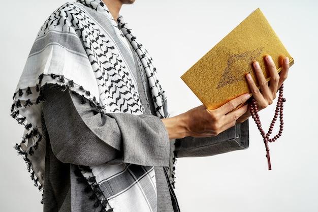 Geste masculin tenant le coran et les perles de prière