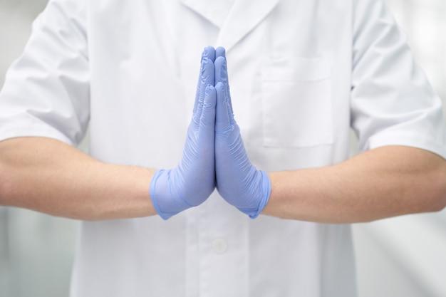Geste namaste fait à la main dans des gants médicaux