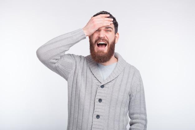 Le geste de la paume du visage est fait par un jeune homme barbu sur blanc.