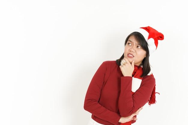 Geste de la pensée de la belle femme asiatique portant un col roulé rouge et un bonnet de noel isolé sur blanc