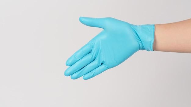Geste de poignée de main portant un gant médical bleu sur fond blanc.
