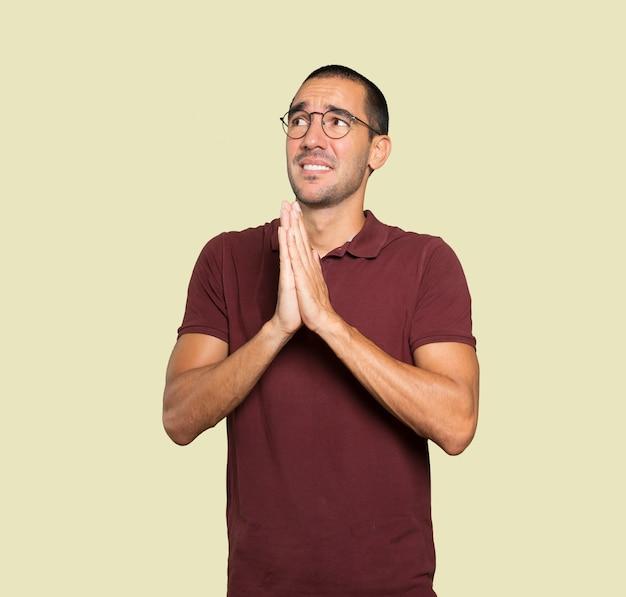 Geste de prière de jeune homme concerné