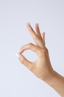 Geste et signe, main féminine sur blanc. doigts montrant ok ou bon