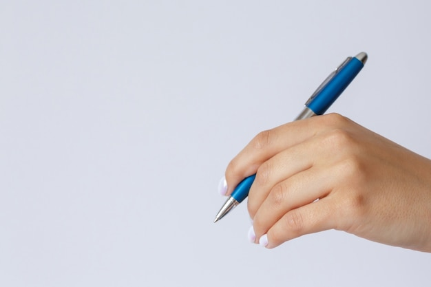Geste et signe la main tenant un stylo sur fond blanc