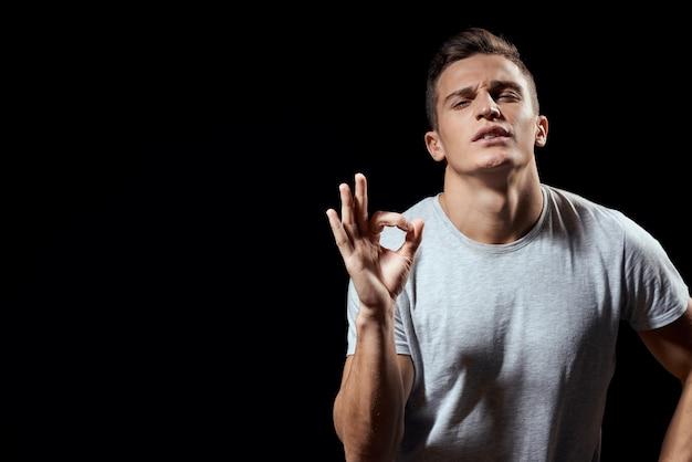 Geste de t-shirt blanc homme gai avec les mains sport fond noir