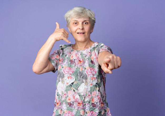 Gestes de femme âgée joyeuse m'appellent signe de la main et points isolés sur mur violet