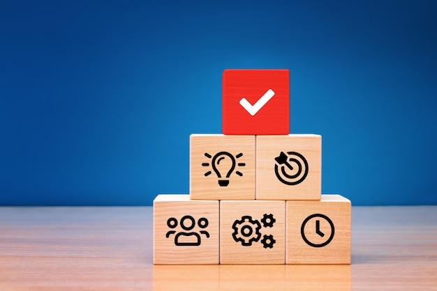 Gestion des processus d'affaires, l'homme d'affaires planifie un projet avec des cubes en bois avec une stratégie commerciale d'icône sur fond bleu.