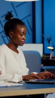 Gestionnaire africain occupé travaillant sur des rapports financiers