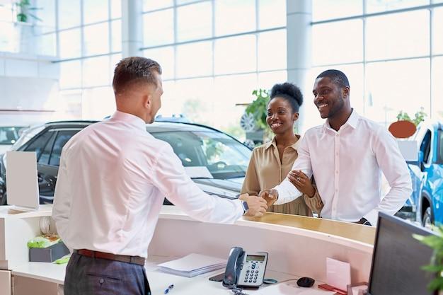 Gestionnaire caucasien sympathique accueillant les clients dans un salon de voiture