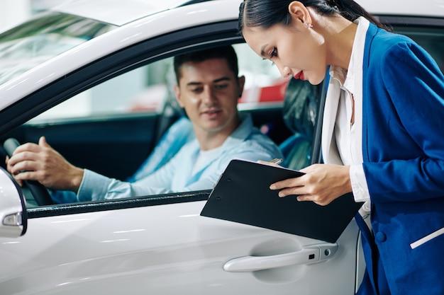 Gestionnaire de concession automobile remplissant les détails du client dans le document avant l'essai routier