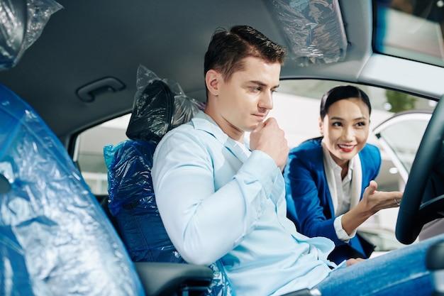 Gestionnaire de concession automobile souriant montrant un compartiment de voiture à un client masculin