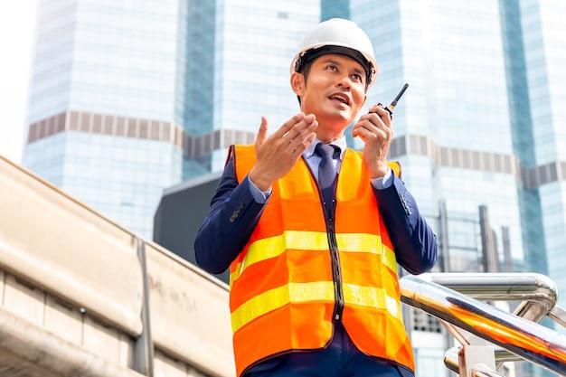 Gestionnaire de la construction asiatique mâle avec l'aide de talkie-walkie sur chantier.