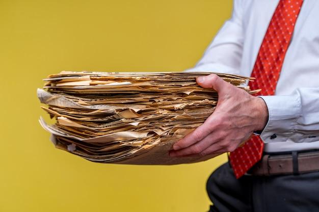 Gestionnaire en cravate rouge donnant une grande pile de documents