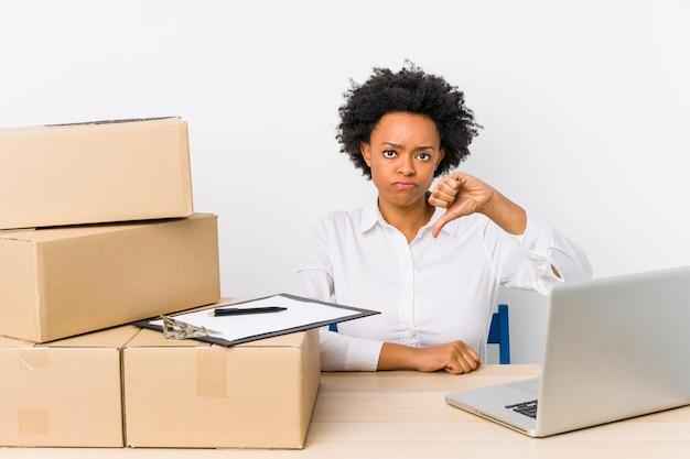 Gestionnaire d'entrepôt assis vérifiant les livraisons avec un ordinateur portable montrant un geste d'aversion, les pouces vers le bas. concept de désaccord.