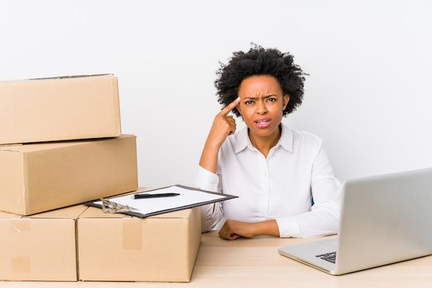 Gestionnaire d'entrepôt assis vérifiant les livraisons avec un ordinateur portable montrant un geste de déception avec l'index