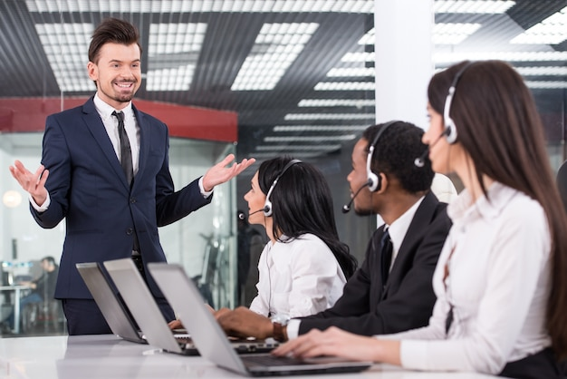 Le gestionnaire explique quelque chose aux employés du centre d'appel.