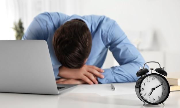 Gestionnaire fatigué avec réveil assis sur le lieu de travail