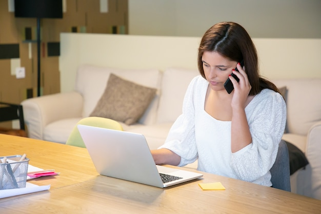 Gestionnaire féminin sérieux discutant du projet avec le client au téléphone, assis à table avec ordinateur portable et plans et dactylographie