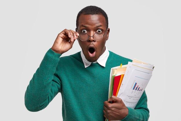 Gestionnaire de marketing masculin prospère avec expression surprise, tient la main sur des lunettes, porte des documents en économie, isolé sur fond blanc