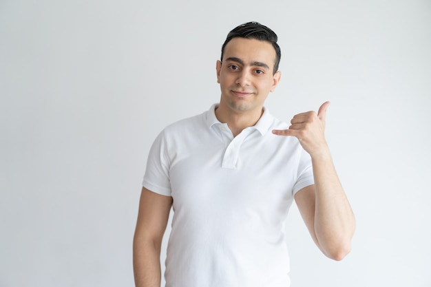 Gestionnaire masculin confiant positif montrant l'appel moi geste et en regardant la caméra.