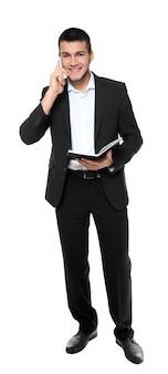 Gestionnaire masculin avec ordinateur portable parlant sur téléphone mobile contre une surface blanche