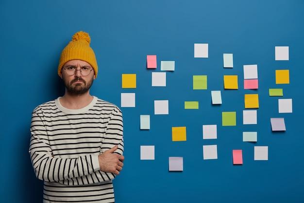 Un gestionnaire masculin qualifié essaie de résoudre le problème du projet, se tient à l'intérieur avec une expression de visage insatisfaite, porte de grandes lunettes rondes