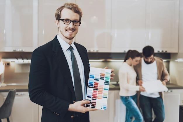Le gestionnaire montre des échantillons de couleur dans un magasin de cuisine.