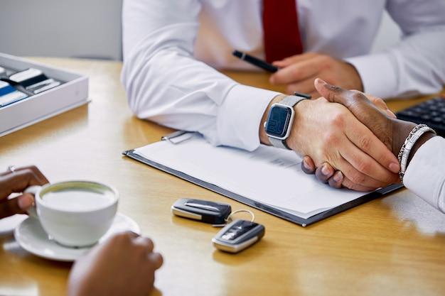 Un gestionnaire professionnel confiant donne les clés de la nouvelle voiture au client et lui serre la main