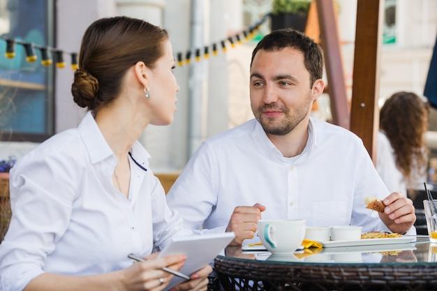 Gestionnaire prospère assis au déjeuner d'affaires avec un collègue