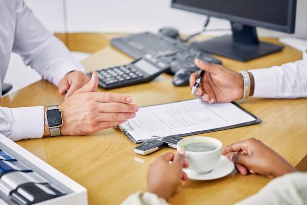 Le gestionnaire serviable du concessionnaire donne les informations et les instructions nécessaires aux clients