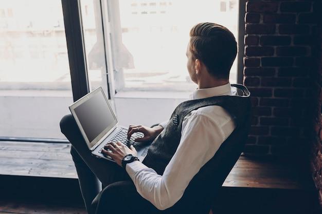 Gestionnaire de sexe masculin adulte travaillant à l'ordinateur portable dans son bureau près d'une fenêtre assis sur une chaise.