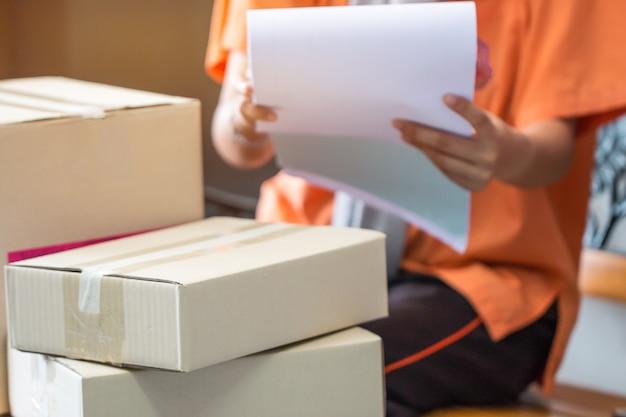 Le gestionnaire signe la vérification des boîtes en carton de la facture de livraison des colis, commande les achats en ligne du client au bureau, prépare le produit de la boîte fabriqué pour la livraison par le livreur à l'acheteur ou au client