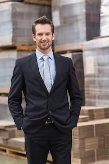 Gestionnaire souriant en costume debout avec les mains dans les poches